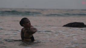 Los ejecutantes de la muchacha bailan trucos acrobáticos en el agua metrajes