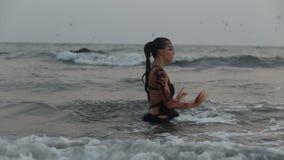 Los ejecutantes de la muchacha bailan trucos acrobáticos en el agua almacen de video