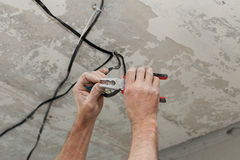 Los electricistas limpian los contactos con los alicates Instalación de la luz de techo imagenes de archivo