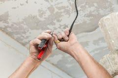 Los electricistas limpian los contactos con los alicates Instalación de la luz de techo fotos de archivo libres de regalías