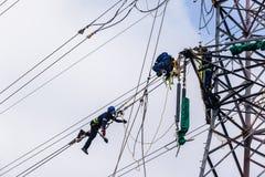 Los electricistas que cuelgan la torre alinean reparaciones Fotografía de archivo