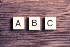 Los elementos de madera con las letras recogieron en el ABC de la palabra Imagen de archivo