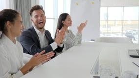 Los empleados aplauden en la oficina, encargados sonríen y aplauden en la tabla en el centro de negocios, unidad de negocio feliz almacen de metraje de vídeo