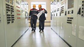 Los empleados caminan a lo largo de los gabinetes de la red que los esquemas del control discuten problemas almacen de video