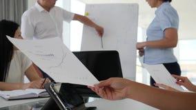 Los empleados cerca del flipchart trabajan con las cartas y ofrecen el desarrollo de negocios de las ideas metrajes