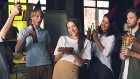 Los empleados de la compañía están celebrando cumpleaños, la mujer está sosteniendo la torta y las velas que soplan, sus compañer almacen de metraje de vídeo
