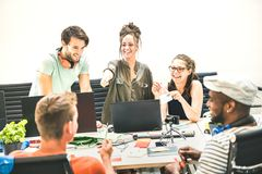 Los empleados de la gente joven agrupan a trabajadores con el ordenador en oficina de lanzamiento imágenes de archivo libres de regalías