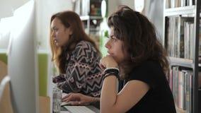 Los empleados de sexo femenino están trabajando cuidadosamente delante de monitores en oficina almacen de video
