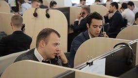 Los empleados de sexo masculino hablan en el teléfono en el centro de atención telefónica de compañía