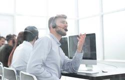Los empleados del centro de atenci?n telef?nica de la imagen de fondo comunican con los clientes imagenes de archivo