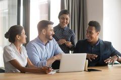 Los empleados diversos sonrientes hablan inspirarse en oficina usando el ordenador port?til imagen de archivo