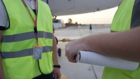 Los empleados en peto amarillo sacuden las manos Los trabajadores del aeropuerto sacuden las manos Los ingenieros sacuden las man imagen de archivo
