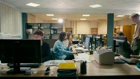 Los empleados están trabajando en la oficina del espacio abierto en el escritorio común con los ordenadores