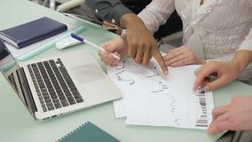 Los empleados jovenes están examinando documentos en la tabla con el ordenador portátil en oficina moderna almacen de metraje de vídeo
