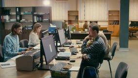 Los empleados jovenes están trabajando juntos en sus ordenadores en la oficina almacen de metraje de vídeo