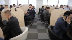 Los empleados jovenes hacen las llamadas, trabajando en el centro de atención telefónica de banco metrajes