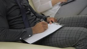 Los empleados jovenes son escritura, sentándose en la conferencia de funcionamiento en oficina moderna dentro almacen de video