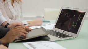 Los empleados jovenes utilizan el ordenador portátil y la tableta, sentándose en compañía principal almacen de metraje de vídeo