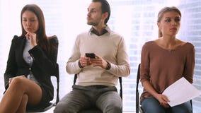 Los empresarios agrupan sentarse en las sillas, esperando concepto de la entrevista de trabajo metrajes