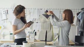 Los empresarios del diseñador de la ropa están midiendo piezas del maniquí mientras que trabajan en estudio moderno agradable Atr almacen de metraje de vídeo