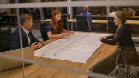 Los empresarios en la tabla miran el papel y hablar almacen de metraje de vídeo