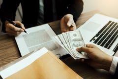 Los empresarios están a punto de firmar un contrato que permita que los socios archiven el efectivo para los sobornos imagen de archivo