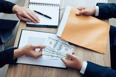 Los empresarios están recibiendo el dinero que es un soborno de sus socios con ambos de los cuales es corrupto en el cuarto de la imagen de archivo