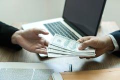 Los empresarios están recibiendo el dinero que es un soborno de sus socios con ambos de los cuales es corrupto en el cuarto de la fotos de archivo