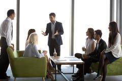 Los empresarios gozan del café que hablan durante la reunión informal de la oficina fotos de archivo libres de regalías