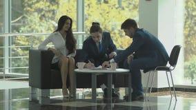 Los empresarios hacen un trato acertado con el encargado en la oficina almacen de metraje de vídeo