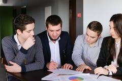 Los empresarios serios, jovenes sirven y la mujer desarrolla los planes para las RRPP foto de archivo