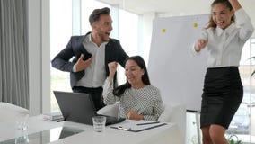 Los encargados felices saltan, la gente acertada joven, equipo acertado del negocio del trato en la oficina moderna, empleados em almacen de video