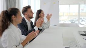 Los encargados sonríen y aplauden en la tabla en el centro de negocios, manos que aplauden de la unidad de negocio feliz en la cá almacen de video