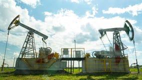Los enchufes potentes de la bomba extraen el petróleo crudo en campo metrajes