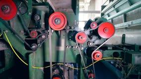 Los engranajes giran en una prensa de batir, mientras que trabaja con la fibra de poliéster almacen de video