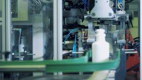 Los envases de plástico blancos están consiguiendo cortados por la máquina de la fábrica almacen de video