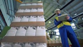 Los envases de plástico están consiguiendo envueltos para arriba bajo control de un inspector de sexo masculino almacen de video