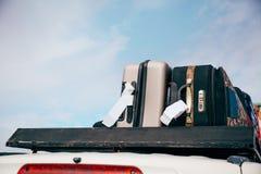 Los equipajes y los bolsos arreglaron en el tejado del coche listo para un viaje en fondo del cielo foto de archivo