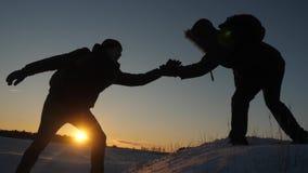 Los escaladores ayudan al estiramiento de la subida del amigo de la mano amiga dos turistas en la parte superior de la montaña Si almacen de metraje de vídeo