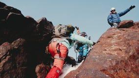 Los escaladores de las muchachas suben la grieta de la montaña al hombre que se coloca en el top Equipan al equipo de las mochila almacen de video