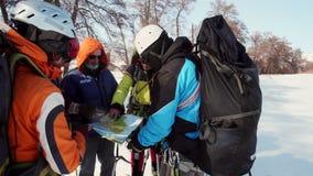 Los escaladores en engranaje lleno hicieron una parada crucial para comprobar la ruta en el mapa y el comp?s, para comprobar outt almacen de video