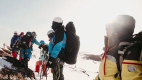 Los escaladores experimentados pararon para un resto encima de las monta?as coronadas de nieve, relajan y traducen la respiraci?n almacen de metraje de vídeo