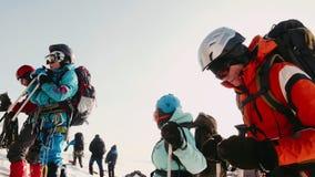 Los escaladores experimentados pararon para un resto, se relajan y reflejan como van arriba Vidrios especiales, casco, mochilas almacen de video