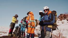 Los escaladores hicieron un paso y están descansando un turista pasa el té de la muchacha de una botella de termo almacen de metraje de vídeo