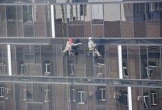 los escaladores industriales limpian ventanas imagen de archivo