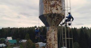 Los escaladores industriales pintan la torre del hierro Trabajo aventurado Trabajo extremo Alpinista del trabajador almacen de metraje de vídeo