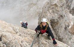 Los escaladores jovenes en una roca escarpada y expuesta hacen frente a que sube vía Ferrata imágenes de archivo libres de regalías