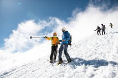 Los escaladores profesionales totalmente equipados descienden abajo de la cuesta nevosa en tiempo soleado Fotografía de archivo