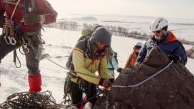 Los escaladores se colocan en una piedra grande y preparan el equipo para la pendiente de la cuerda almacen de video