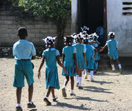 Los escolares y las muchachas se apresuran de nuevo a clase en Robillard, Haití Imagen de archivo libre de regalías